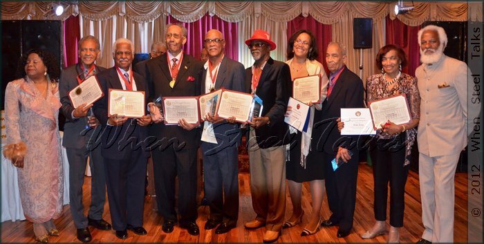 Honored Steelband pioneers and proxies hold awards at the end of the evening