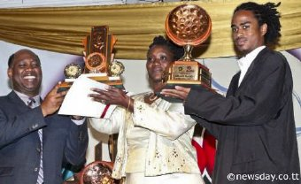 Norman Christie, left, president BpTT, presents the awards for Small Bands PanoramaChampion 2013 to Carlene Thomas and Daryll Bernard of Arima Golden Symphony