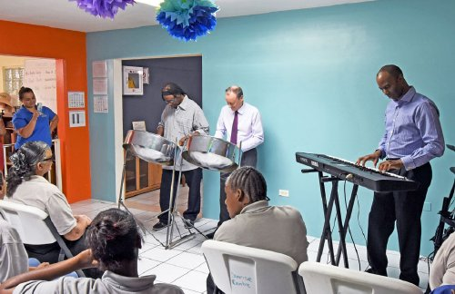 Earl La Pierre, left, Governor Martyn Roper and Glen Inanga perform for the Sunrise Centre