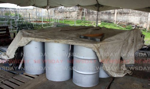 A tarpaulin drapes over the bass pans at the Desperadoes Steel Orchestra on Tragarete Road, Port of Spain